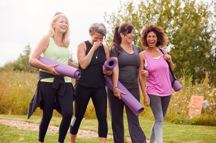 Four women carrying yoga mats.