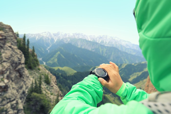 A hiker checks her smartwatch with mountains in the background