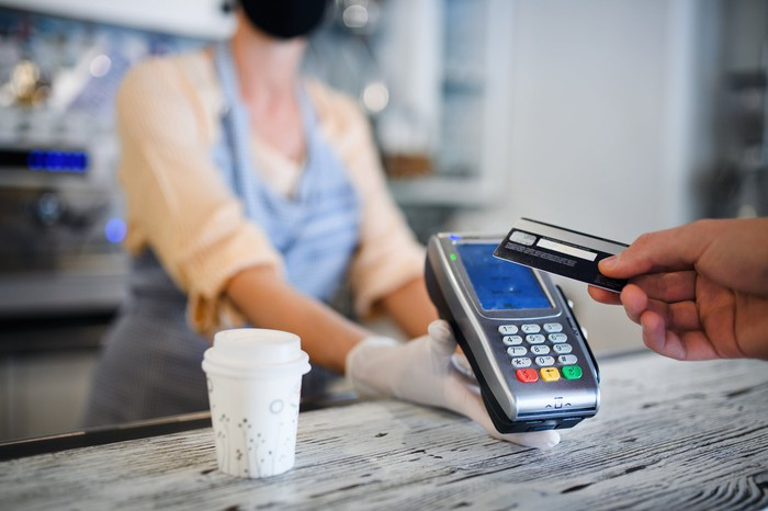 A merchant wearing a mask holds out card swiper for buyer using credit card
