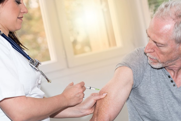 Nurse injecting older person.