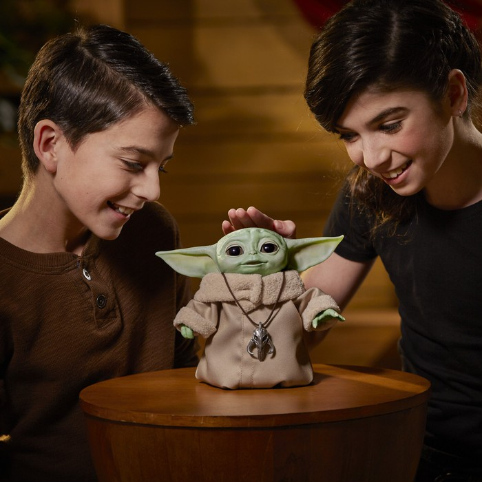 A young boy and girl playing with a Baby Yoda toy.