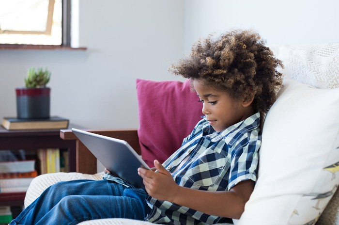 Young person using a tablet at home.