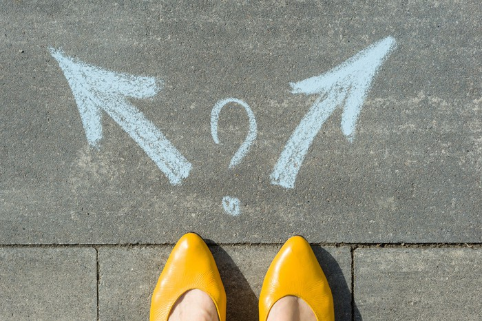 A woman's shoes stand in front of two arrows pointing in opposite directions, with a question mark between the arrows.