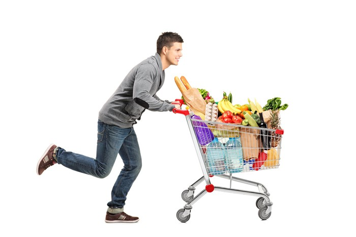 Young man running with a full grocery cart.