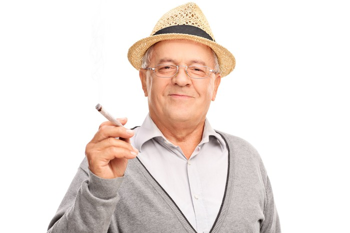 An older man in a hat holds a joint and smiles into camera.