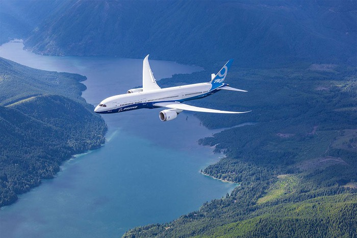 A Boeing 787-9 flying over a river.