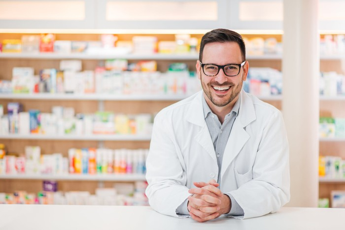 Smiling male pharmacist wearing a lab coat and leaning on pharmacy counter.