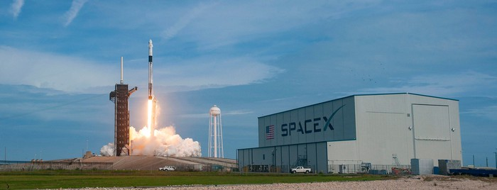 Falcon 9 rocket launch with SpaceX hangar in the foreground.