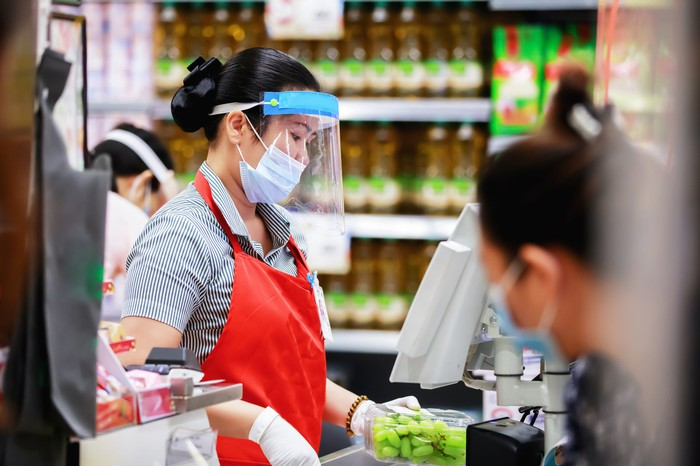 Woman scanning food at register, wearing a mask and gloves.
