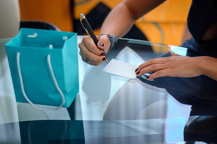A person signs a slip of paper next to a turquoise shopping bag.