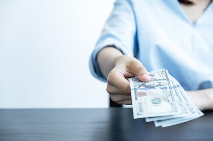 Person handing over dollar bills.