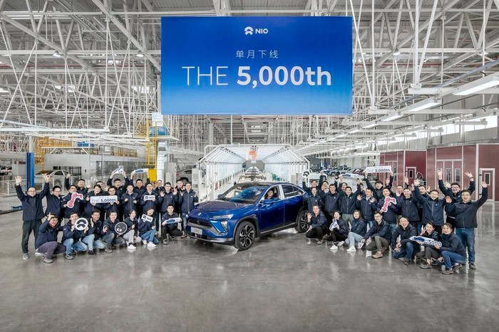 Auto workers are shown gathered around a NIO EC6, below a banner marking the 5,000th car built in October.