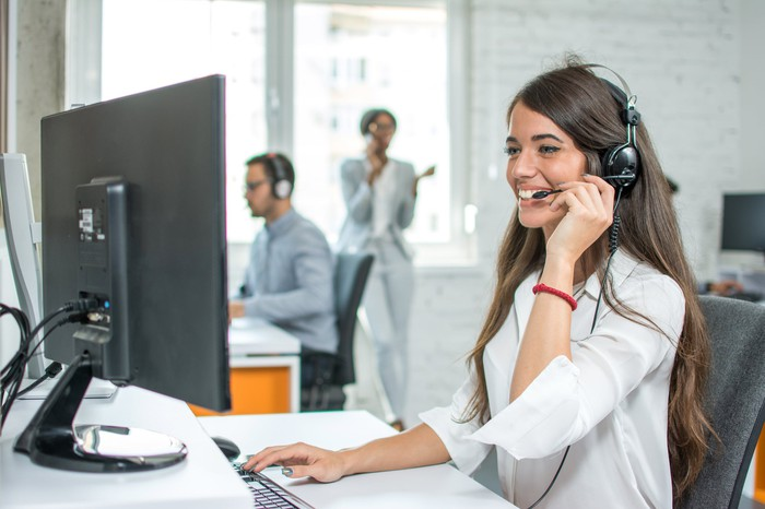 Woman sitting at computer and talking on headset