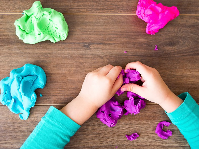 A child's hands working with play doh.