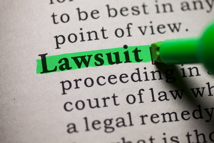 A person highlighting in green the word lawsuit in a document.