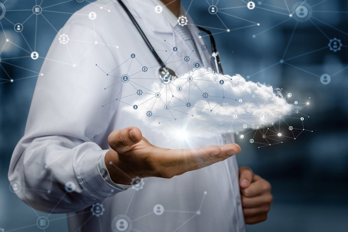 Doctor with 3-D cloud hovering over his hand.