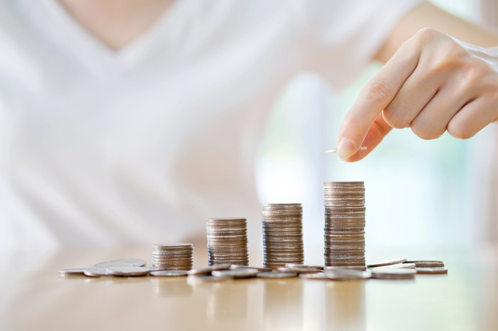 A casually dressed young person stacks coins in piles of rising height.