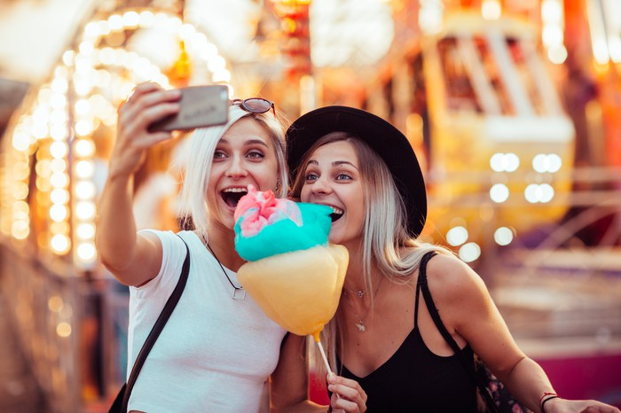 Two women taking a selfie with cotton candy at a theme park.
