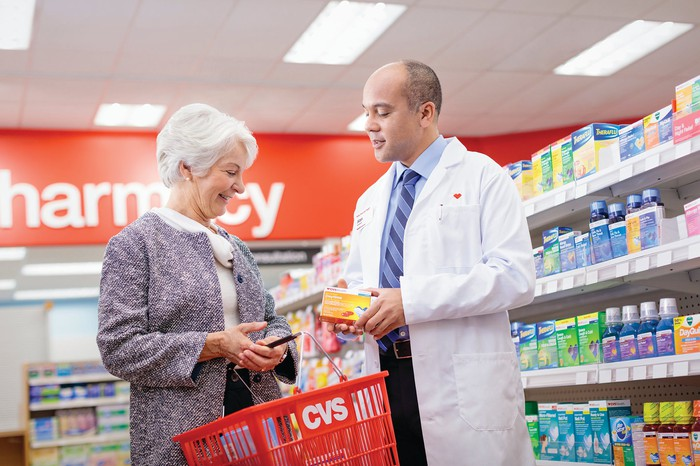 A CVS pharmacist helping a senior woman with a purchase.
