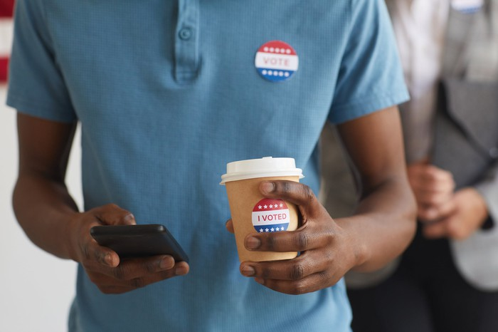 Torso of a man using a smartphone, with election-related stickers on his shirt and on a takeout coffee he's holding.
