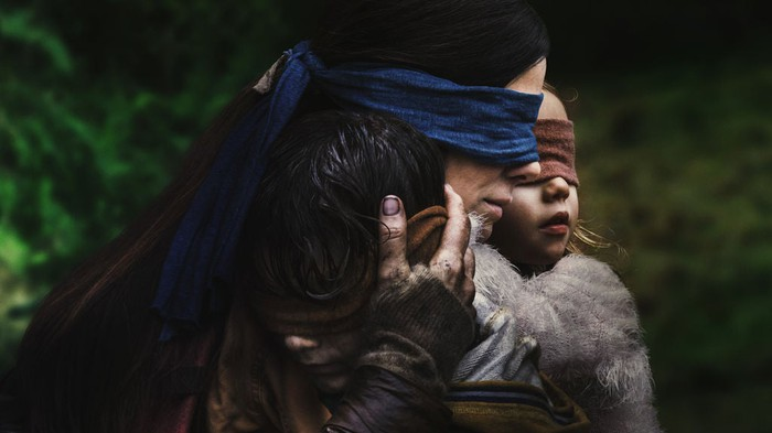 Sandra Bullock in Bird Box, blindfolded as she carries a young blindfolded girl.