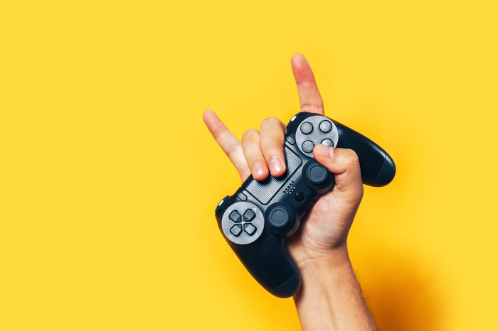 A man holds up a PlayStation controller.