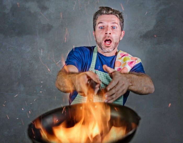 Man with frying pan on fire