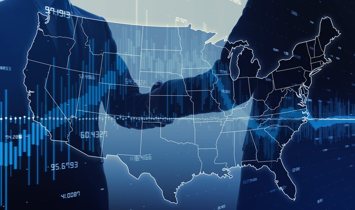 Two politicians shaking hands superimposed on a U.S. map and stock chart.
