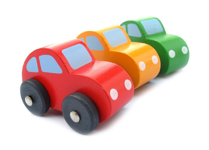 Three brightly colored toy cars in a row