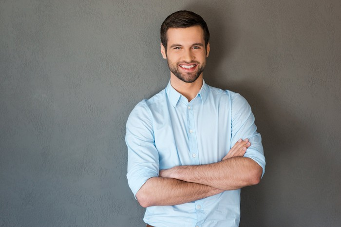 Smiling man in dress shirt against gray background