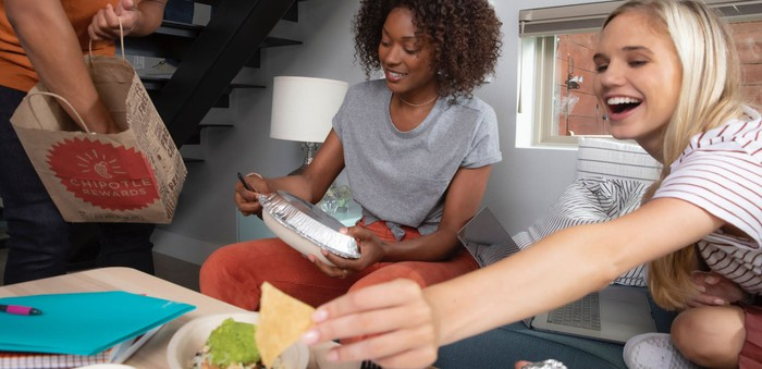 Three people enjoying menu items from Chipotle Mexican Grill at home.
