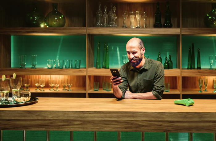 Merchant leaning on a counter with glassware on shelves behind him and a Stone card-reading machine next to him