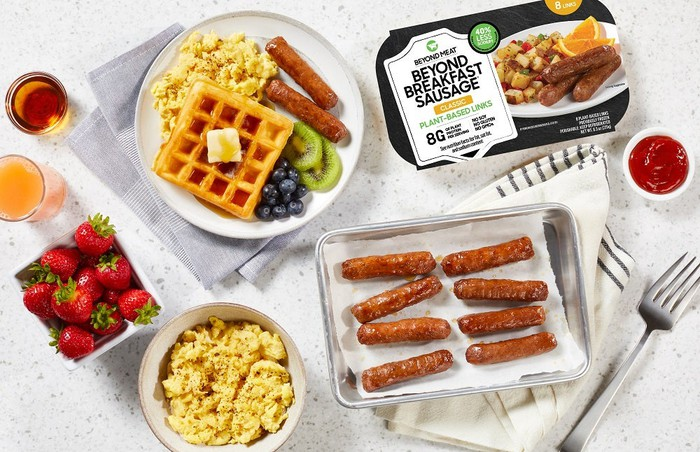 A table is set with typical American breakfast items, including Beyond Breakfast Sausage Links by Beyond Meat and its commercial packaging.
