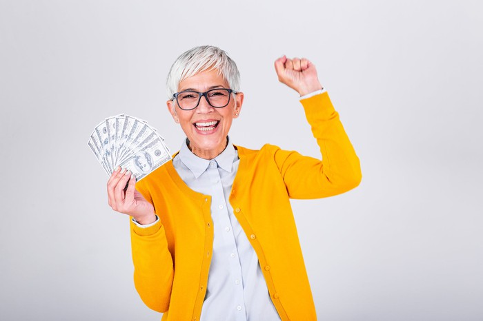 Senior woman holding cash and smiling.