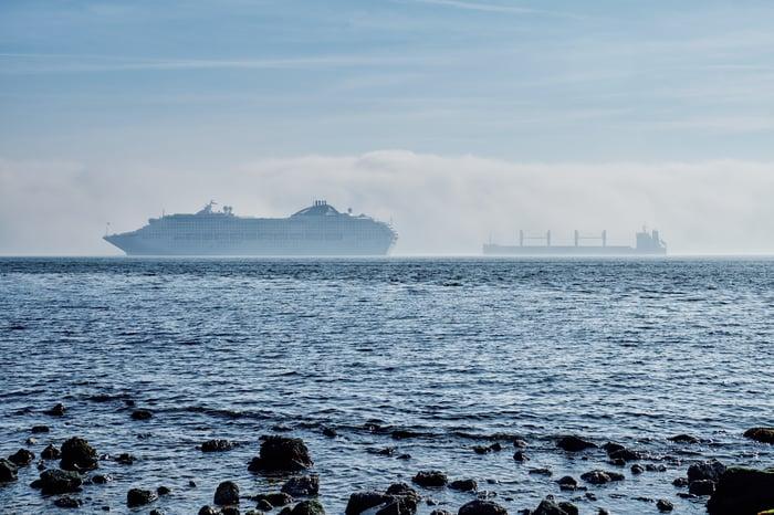 A cruise ship seen through a sea mist, passing a cargo vessel, off Lisbon, Spain.