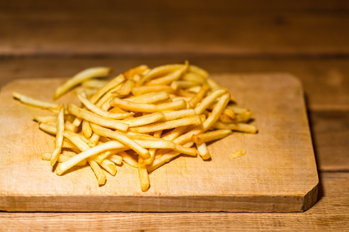 A batch of French fries on a cutting board.