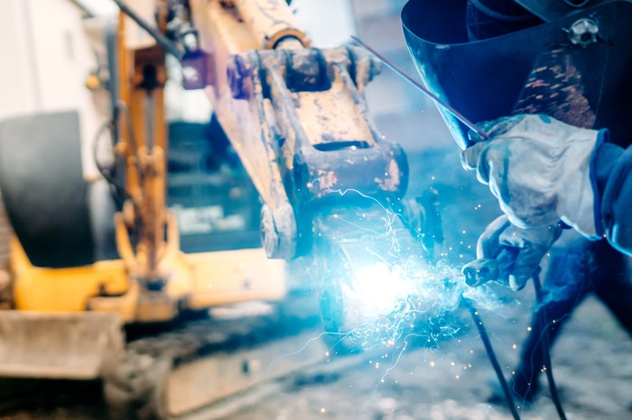 A welder works on industrial machinery at a construction site.
