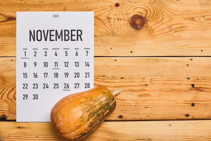 A gourd and November calendar on a wooden background.