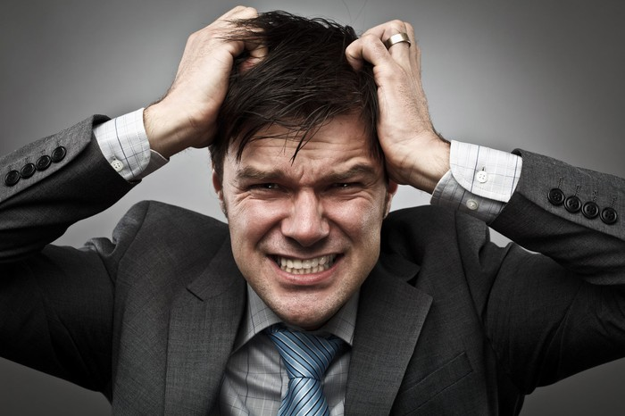 Businessman with hands on head with panicked expression on face.