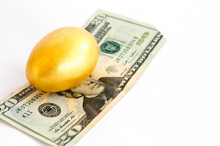 A golden egg on top of a twenty-dollar bill.