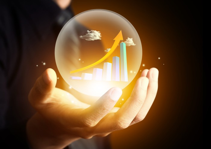 Hand holding crystal ball with upward stock chart and arrow inside
