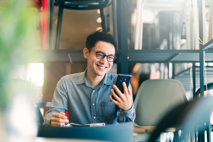 A young man in glasses smiles at  his smartphone sitting  at a table.