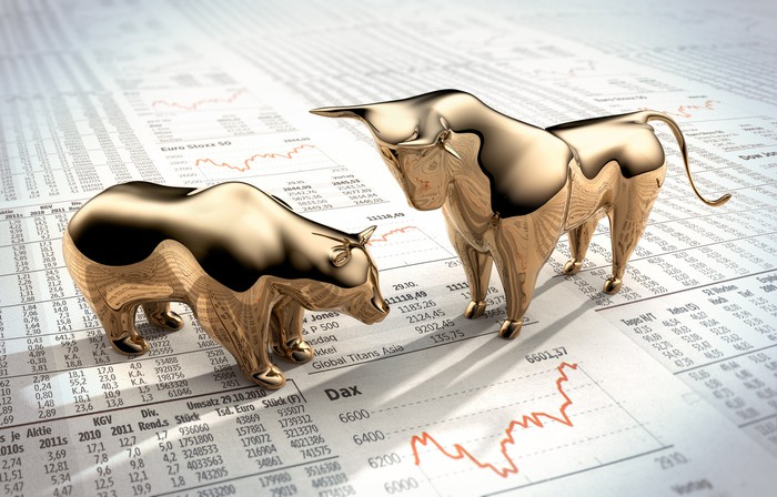 Two miniature figurines of a golden bull and bear standing on a sheet showing a list of stock quotes.