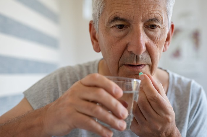 Older man holding pill in one hand and glass in the other