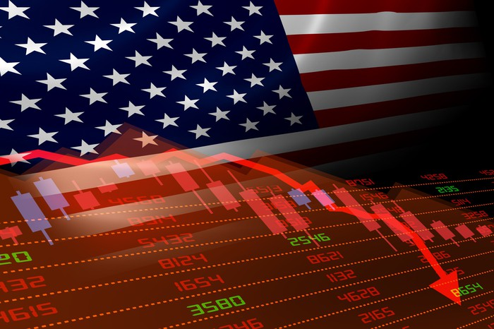 Stock charts going down with U.S. flag in background