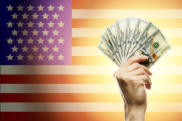 Hand holding $100 bills in front of a U.S. flag