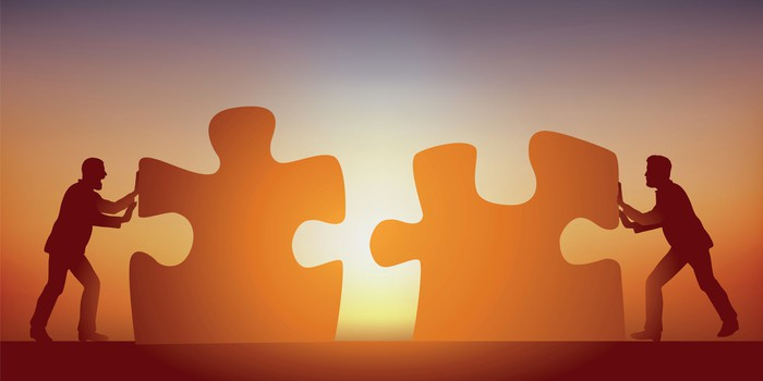 Silhouettes of people pushing two giant jigsaw puzzle pieces together with the sun shining in the background