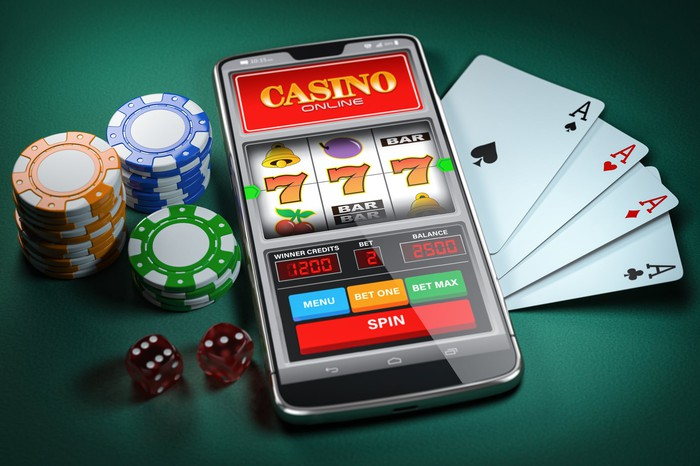 Slot machine on smartphone screen, cards, dice, and poker chips