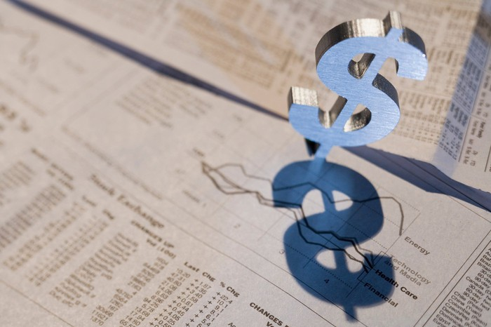 A dollar sign popping up out of a financial newspaper that has visible stock quotes.