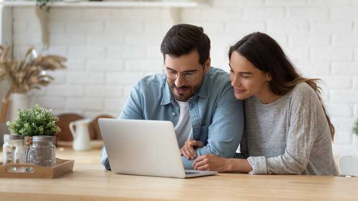 Sitting at a kitchen table, a man and woman look at a laptop.